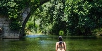 Una mujer metida dentro de la piscina natural de Carreciá mira hacia el puente con el mismo nombre y la vegetación que lo envuelve.