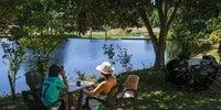 Una mujer y un niño se toman algo en la terraza de un chiringuito con vistas a la piscina natural de Los Pilares.