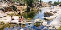 Varias personas toman el sol mientras otros se bañan en la zona más salvaje de la piscina de Jever