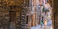 Una mujer y un niño caminan por una de las calles estrechas de Robledillo de Gata, uno de los pueblos más bonitos de España.