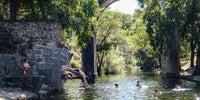 Un joven se lanza de cabeza al agua en la piscina natural de Perales del Puerto, con el puente al fondo.
