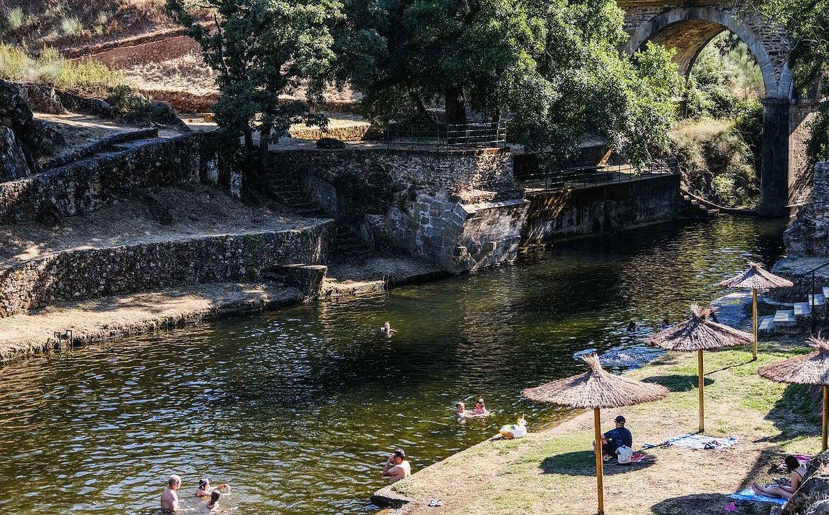 Vista general de la piscina natural Perales del Puerto, con el agua a un lado y las sombrillas y zonas verdes al otro.