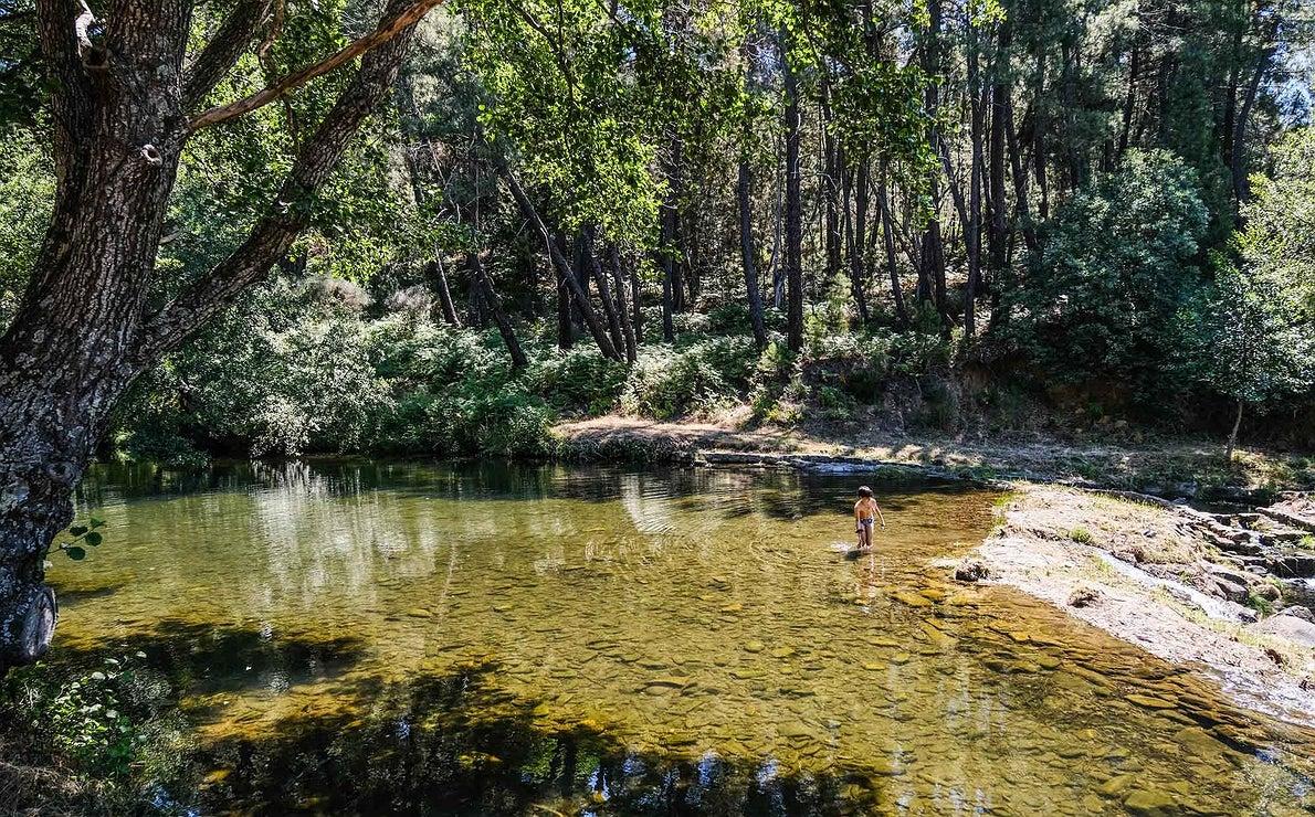 Un niño se baña en un remanso de aguas cristalinas y lecho pedregoso del río Arrago.