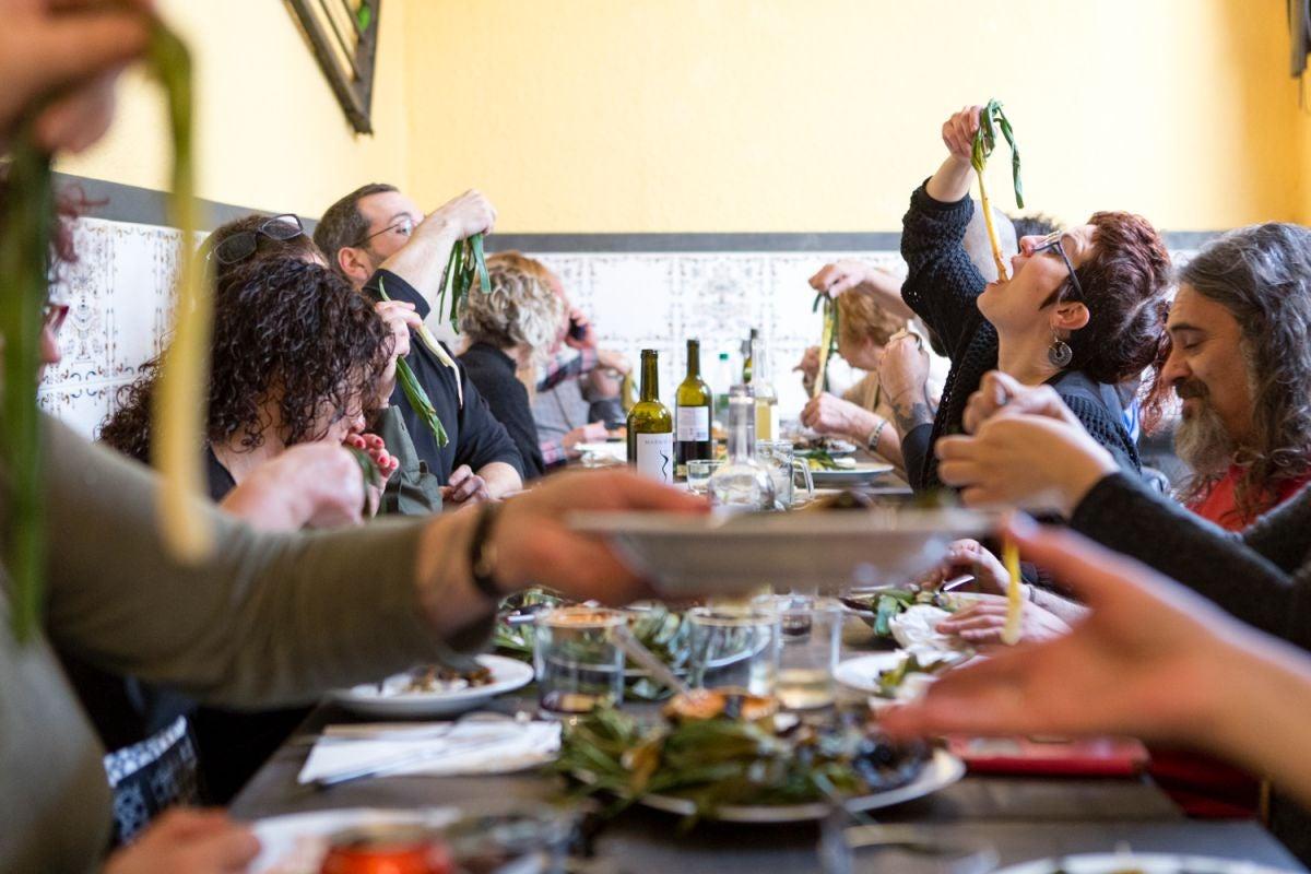 El 'baile' de los calçots sobre una mesa de amigos en 'La Taina'.