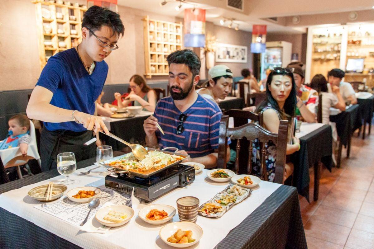 Sala del restaurante coreano, Soban, en Barcelona con un plato de Dak kalvi sobre la mesa de un comensal.