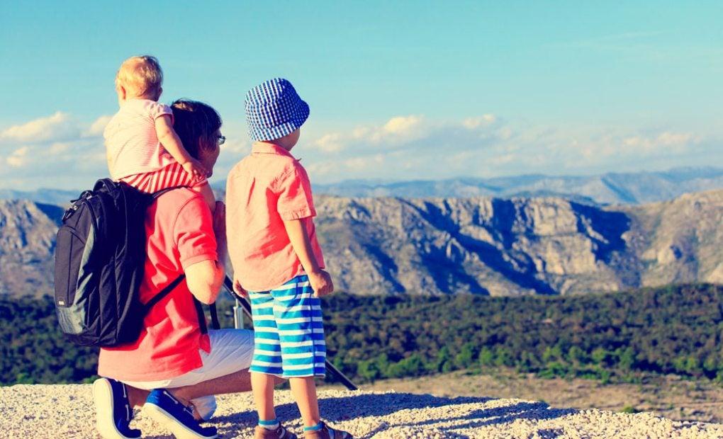 Un padre con sus dos hijos en lo alto de una montaña. Foto: shutterstock.