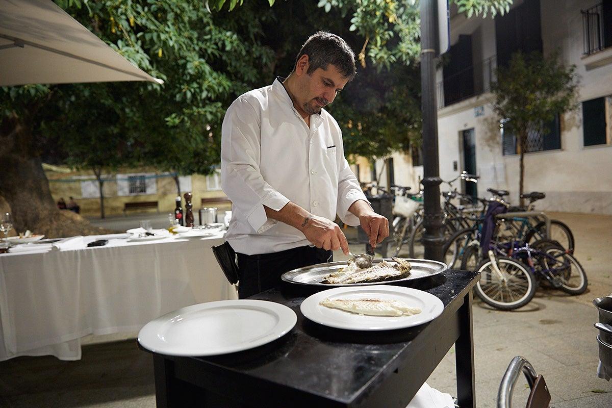 En la terraza, preparando el pescado antes de servirlo.