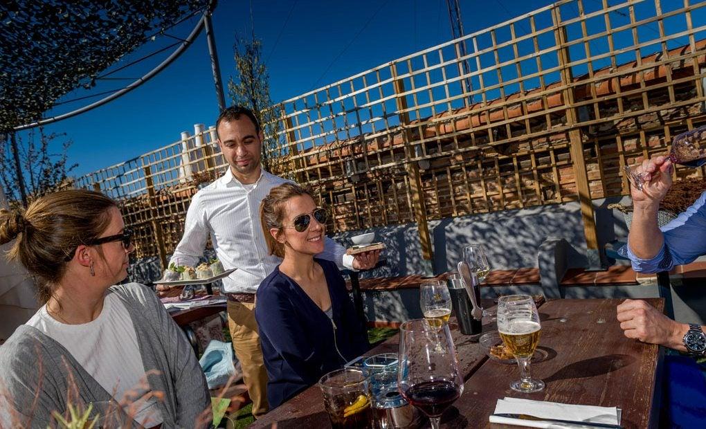 Un camarero sirve comida a tres personas sentadas en una mesa en el Paracaidista