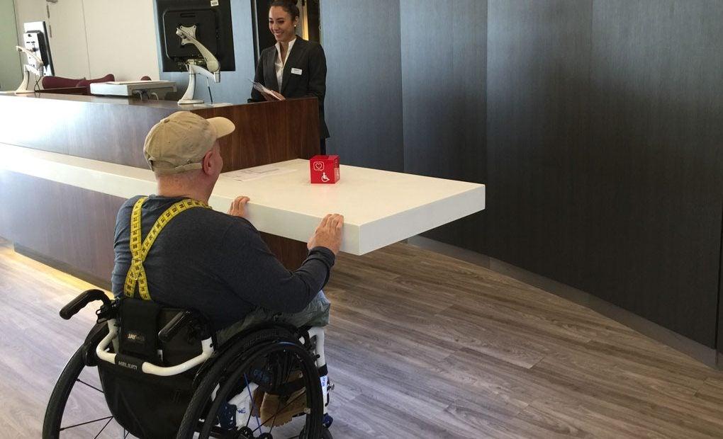 Hombre en silla de ruedas en la recepción de un hotel sostenible