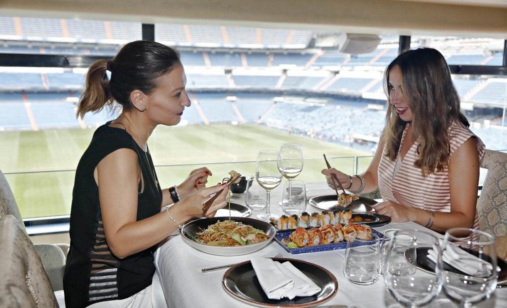 Dos mujeres comiendo con vistas al campo del Bernabéu
