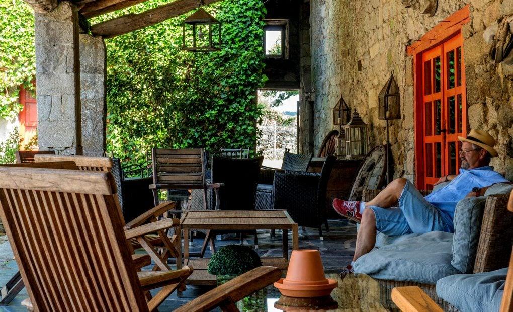 Persona sentada en la terraza de un pazo reconvertido en un hotel rural.