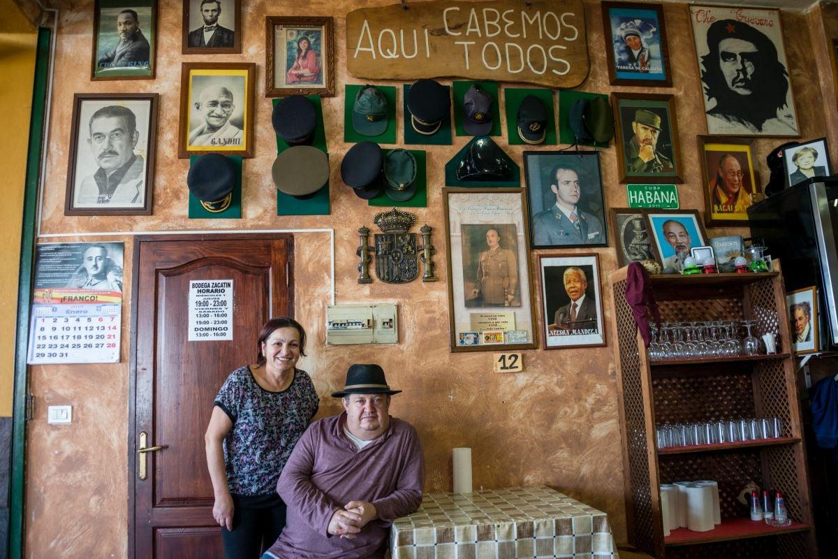 El matrimonio propietario del guachinche Bodega El Zacatín, Eladio y Nina, en Tenerife, posando junto a la pared donde cuelgan fotos de los más dispares dirigentes políticos.