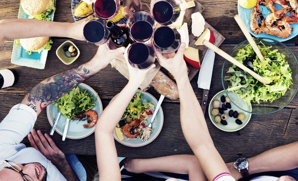 Personas brindando con vino tinto