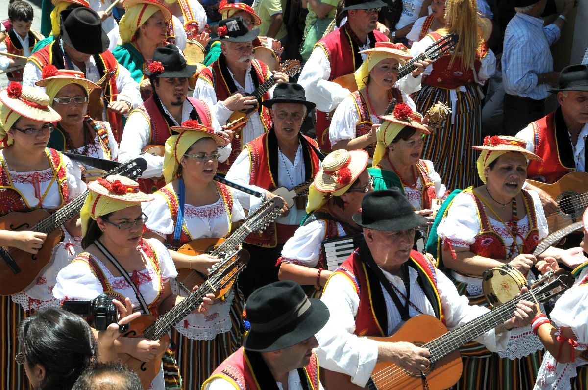 Un grupo de personas tocan y cantan folclore canario durante la Romería de San Isidro Labrador de La Orotava, en Tenerife.