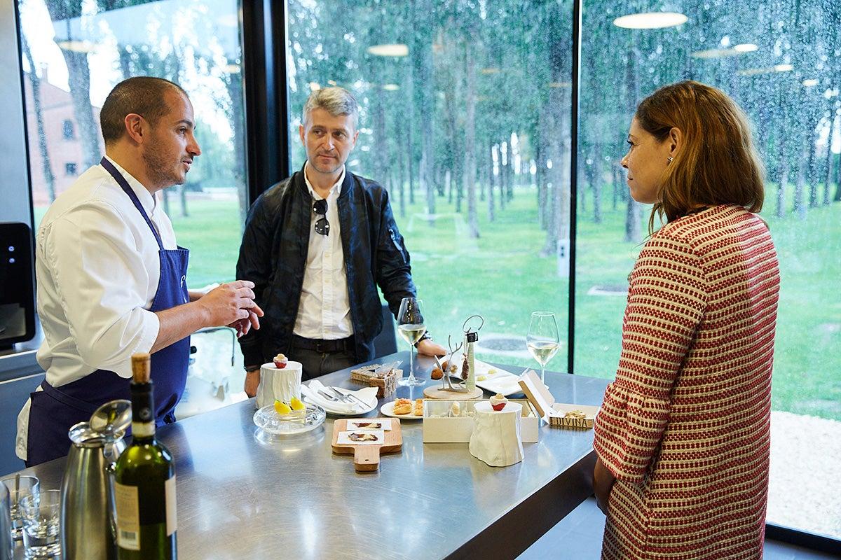 El chef Joël Castanyé explica a dos clientes los aperitivos.