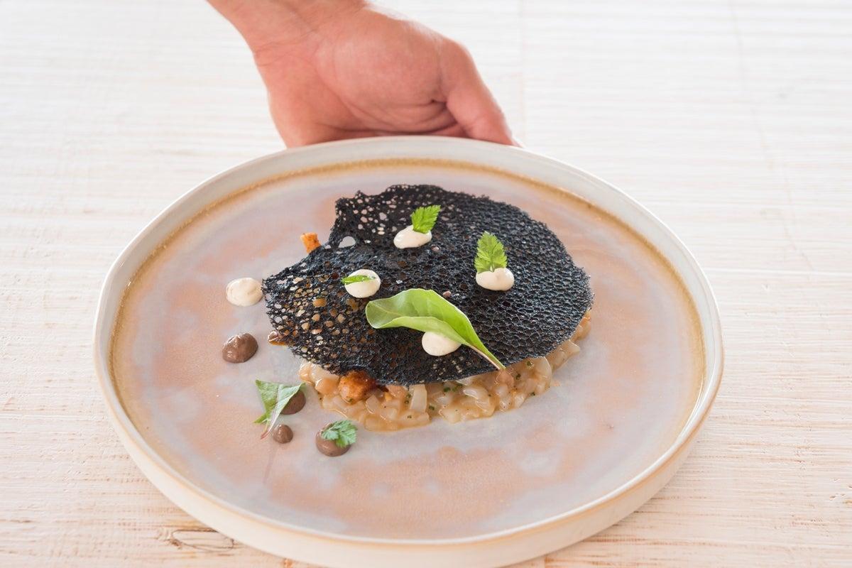 Tartar de calamar con aliño de reducción de sus interiores y lima kaffir cubierto con crujiente de tinta, de 'Blue Fish'.