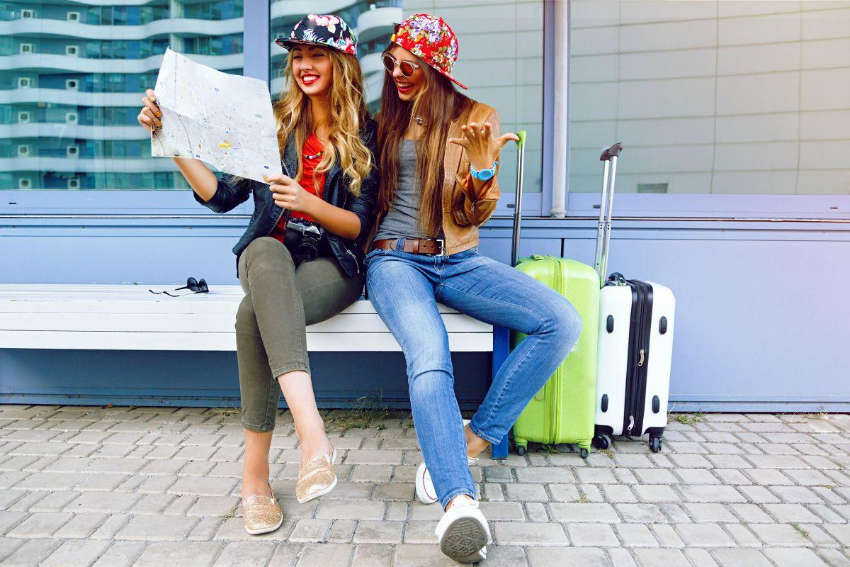Dos jóvenes viajeras con maletas mirando un mapa.