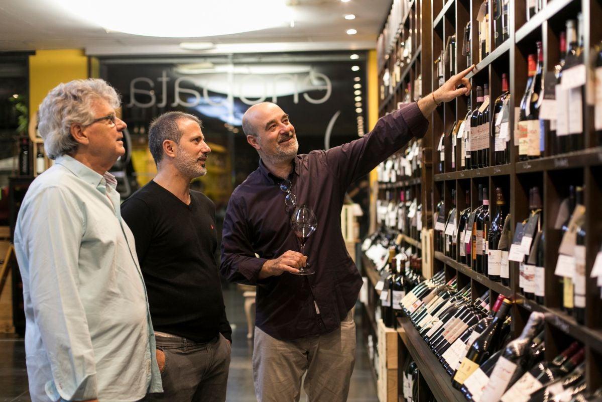 Apertura. Los clientes de la vinoteca Enópata miran las botellas expuestas en la tienda (Valencia). Foto: Eva Máñez