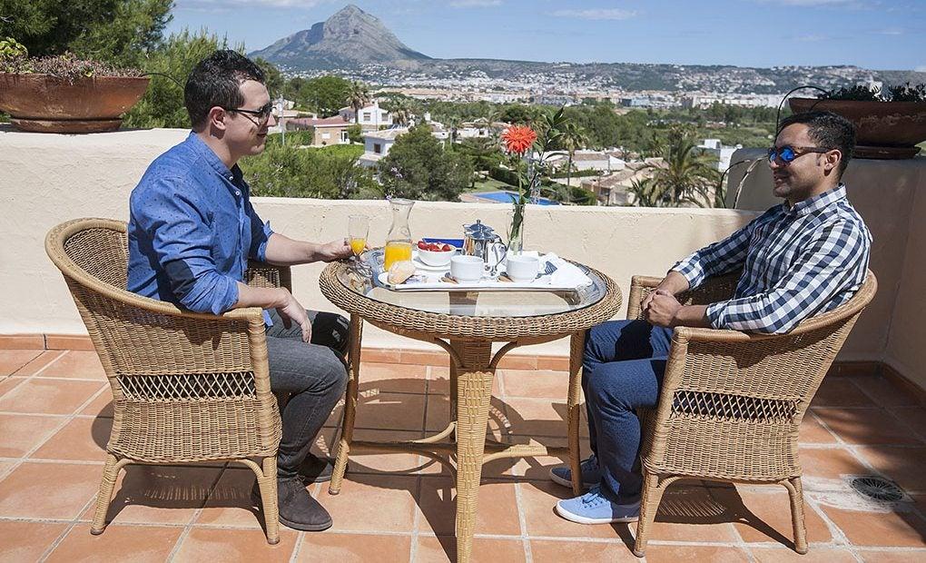 Dos hombres sentados desayunando en una de las terrazas de las gran suites que tienen vistas al monte Montgó