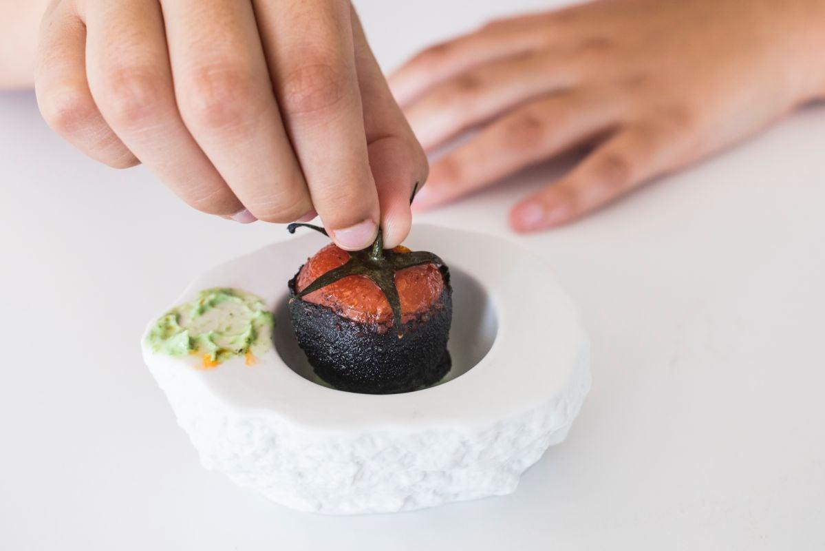 Plato de Tomate cherry en rama relleno de chorizo y kimchi en tempura de tinta de calamar con una emulsión de salvia y menta del restaurante 'La Sucursal', en Valencia.