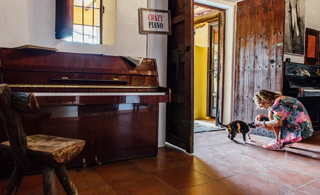 Sofía, una de las empleadas, acaricia uno de los gatos de Anthony Pike, en el hall de entrada a la habitación de Freddie Mercury