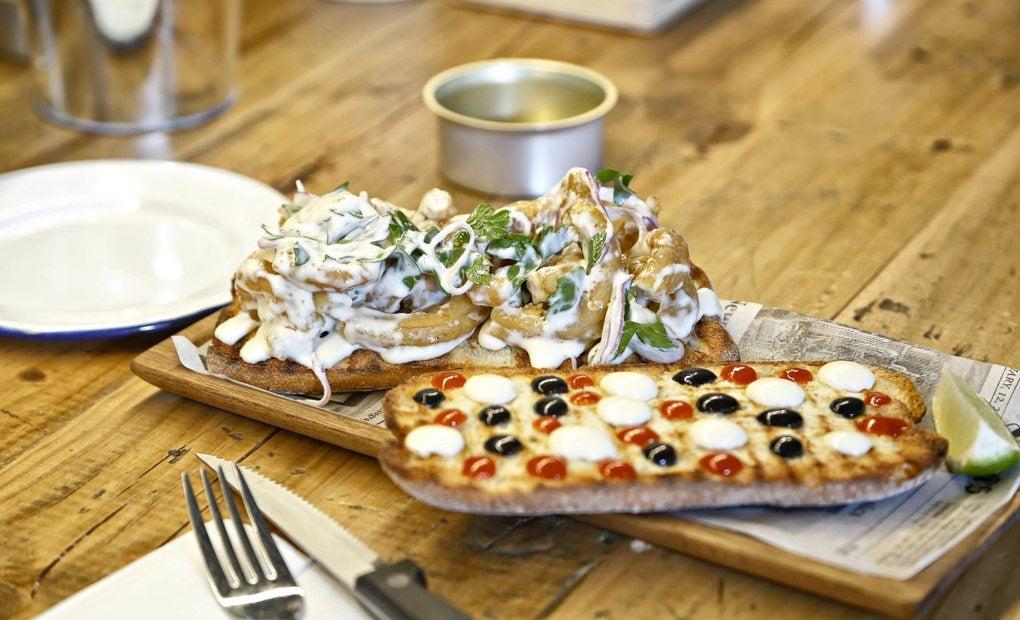 El bocadillo de chapata de ajo, calamares, mayonesa blanca y negra, perejil y lima.