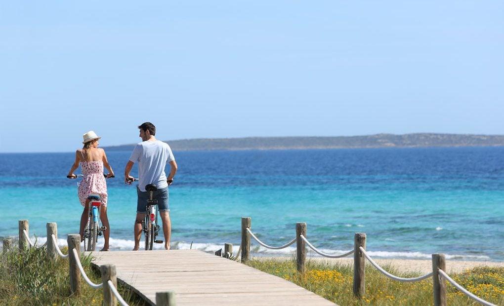 Una pareja montando en bicicleta camino de la playa.