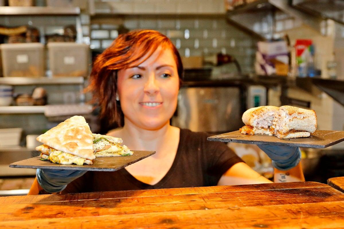 Una camarera de la sandwichería 'Magasand', en Madrid, mostrando dos de sus sándwiches.