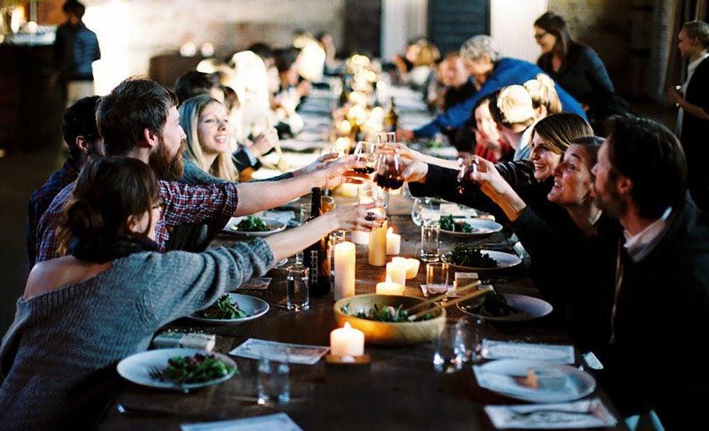 Personas en una mesa brindando con pacharán.